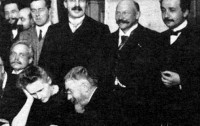 Henri Poincaré discute algo con Marie Sklodowska Curie mientras detrás, de pie, está Albert Einstein en la foto oficial de la Conferencia Solvay de 1911.